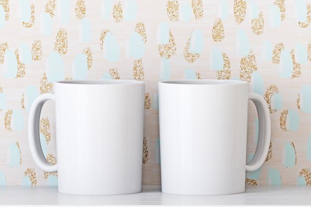 Maqueta de dos tazas blancas sobre un fondo de papel tapiz claro