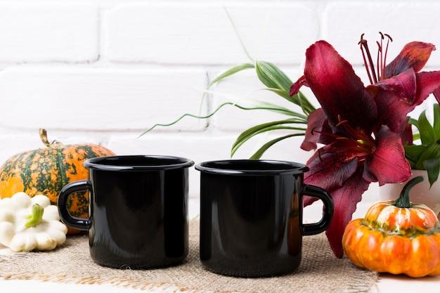 Maqueta de dos tazas de esmalte de fogata negra con calabaza y lirio rojo