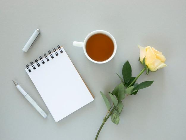 Maqueta de escritorio festiva. flor color de rosa, taza de té y cuaderno de espiral de papel en blanco con espacio para saludos. concepto de vacaciones