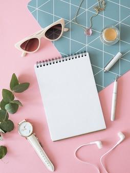 Maqueta de escritorio de moda femenina plana. copie el espacio en un cuaderno de espiral, rama de eucalipto y gafas de sol sobre una mesa rosa. vertical.