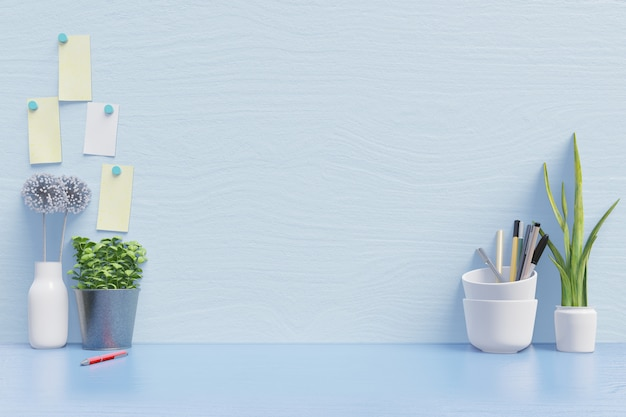 Maqueta de espacio de trabajo para computadora portátil en el escritorio y para trabajar con la decoración en la pared azul del escritorio