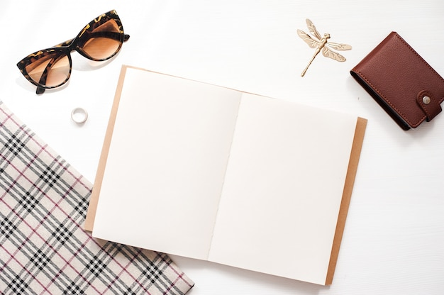 Maqueta del espacio de trabajo de la oficina en casa con gafas, billetera y accesorios para mujer, cuaderno