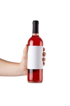 Maqueta de etiqueta blanca en blanco en una botella de vino tinto en la mano