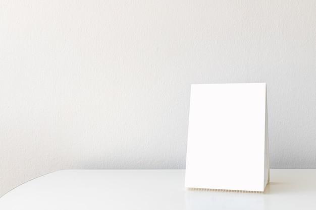 Maqueta etiqueta el marco del menú en blanco en el restaurante bar. soporte para folleto con tarjeta de carpa acrílica de papel blanco en la mesa con fondo borroso que puede insertar el texto o la imagen.