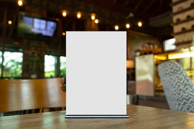 Maqueta etiqueta el marco del menú en blanco en el restaurante bar. soporte para folleto con tarjeta de carpa acrílica de papel blanco en la mesa con fondo borroso que puede insertar el texto o la imagen