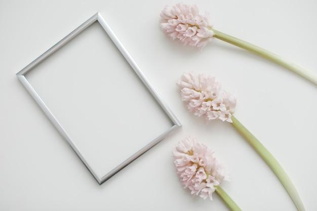 Maqueta con flores rosas y marco de fotos en blanco con espacio de copia.