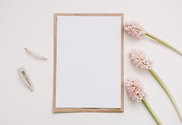 Maqueta con flores rosas y papel en blanco