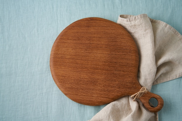 Maqueta de fondo de alimentos con tabla de cortar de madera redonda sobre fondo de mantel textil de lino azul