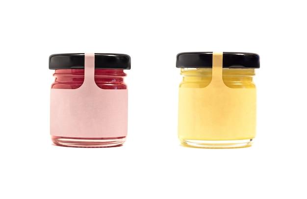 Maqueta de frascos de vidrio con miel, mermelada u otro producto conservado con etiqueta de papel aislado en blanco
