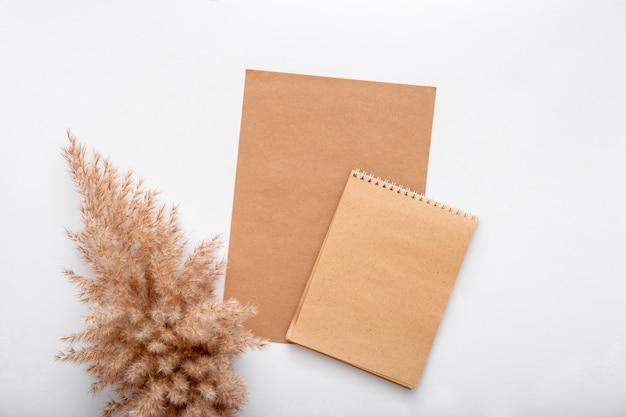 Maqueta de invitación de nota de tarjeta de papel artesanal en blanco de color beige terroso con flor seca rama de pampas de caña. bloc de notas de maqueta marrón en blanco para tarjeta de felicitación. espacio elegante con marco de maqueta sobre fondo blanco.