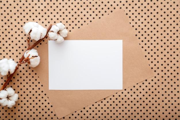 Maqueta de invitación de nota de tarjeta de papel en blanco blanco con rama de flores de algodón de floración. maqueta en blanco para tarjetas de felicitación de boda. espacio elegante con maqueta blanca en marco de color beige earthy craft. endecha plana.