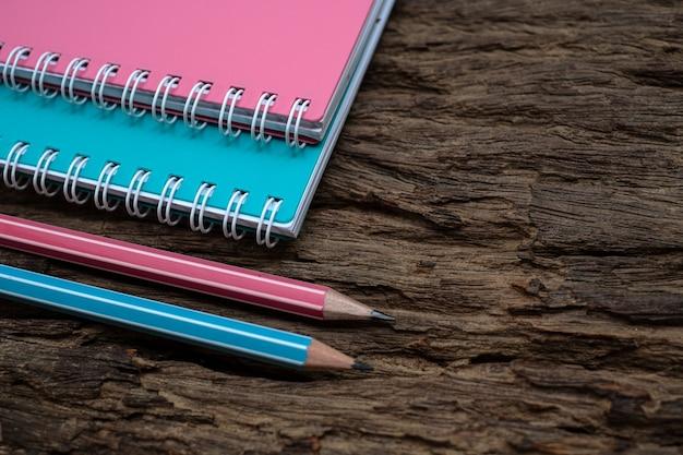 Maqueta de lápiz y libro sobre el viejo escritorio de madera en el fondo