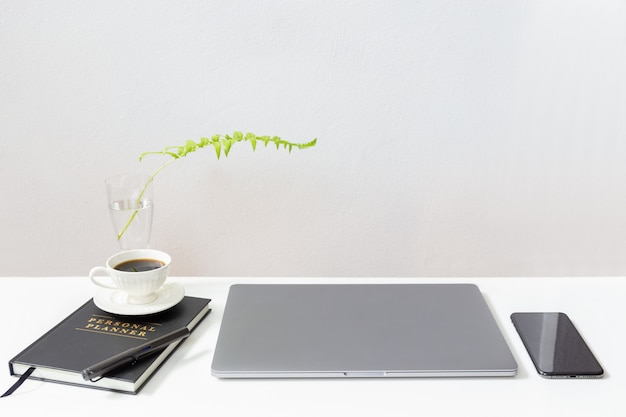 Maqueta de laptop con taza de café sobre portátiles y teléfono celular en mesa blanca.