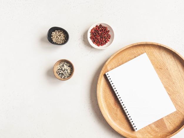 Maqueta de libreta de cocina para texto culinario en bandeja de madera y especias