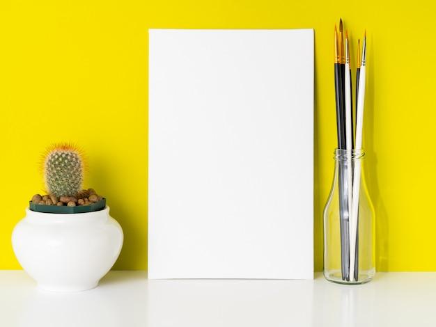 Maqueta con lienzo blanco limpio, cactus, pinceles sobre fondo amarillo brillante. concepto para c