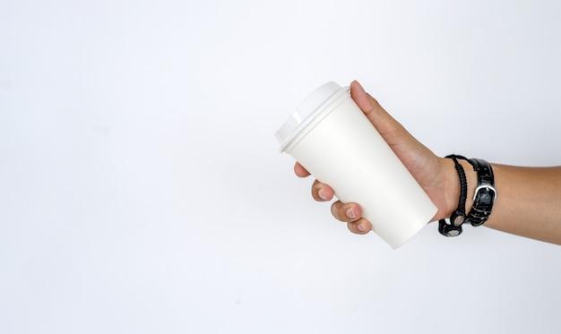Maqueta de la mano masculina que sostiene una taza de café caliente en el fondo blanco