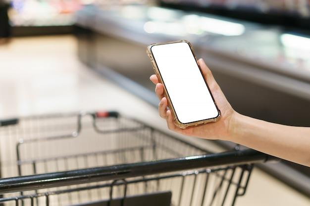 Maqueta, manos sosteniendo un teléfono móvil de pantalla blanca en blanco con carrito de compras en el supermercado