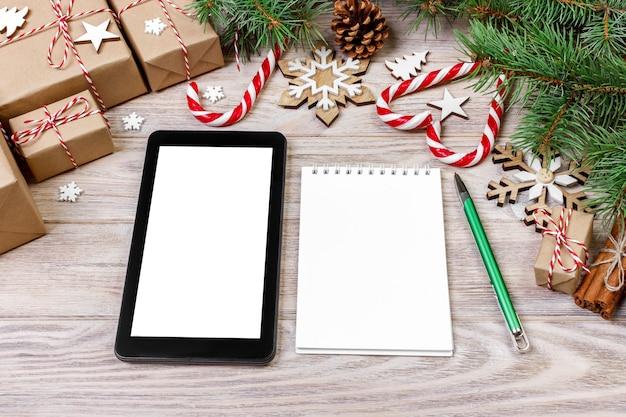 Maqueta de la marca de la tableta portátil para la época navideña, decoración navideña sobre fondo blanco, vista superior plana.