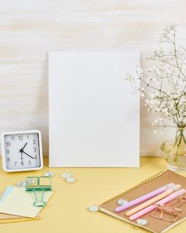 Maqueta con el marco blanco en blanco en la mesa amarilla contra la pared de madera, alarma, flor en vaze