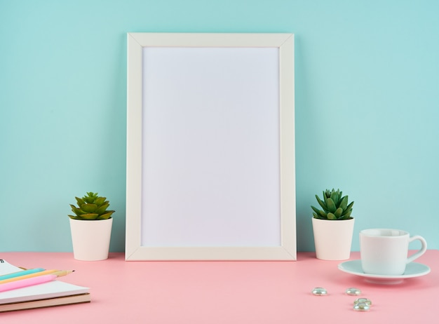 Maqueta con marco blanco en blanco, planta de cactus, taza de café o té en mesa rosa contra pared azul