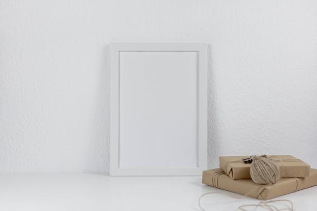 Maqueta de marco en blanco blanco con regalos envueltos en navidad