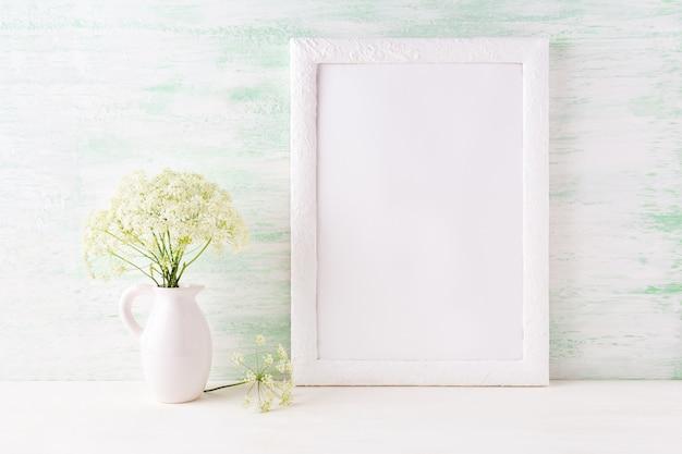 Maqueta de marco blanco con delicadas flores silvestres en la jarra