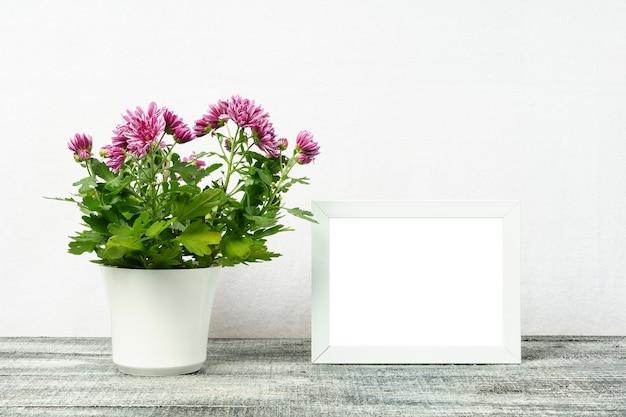 Maqueta de un marco blanco con una flor de crisantemo en una maceta blanca sobre una mesa de madera.