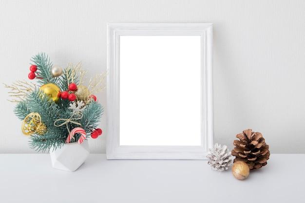 Maqueta de marco blanco de madera vacía con ramo de año nuevo en el interior de la habitación blanca
