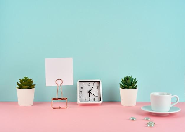 Maqueta con marco blanco, nota, alarma, taza de café o té en una mesa rosa contra una pared azul