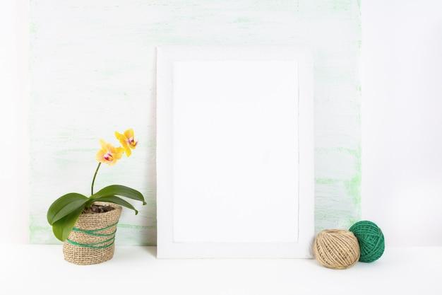 Maqueta de marco blanco con orquídea amarilla
