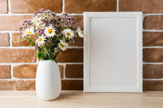 Maqueta de marco blanco con ramo de flores silvestres cerca de la pared de ladrillo a la vista