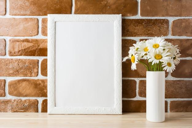 Maqueta de marco blanco con ramo de margaritas cerca de la pared de ladrillos expuestos
