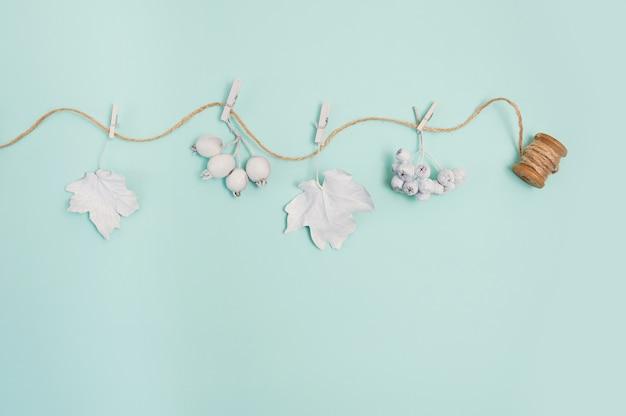 Maqueta de marco con calabaza, bayas, cuerda y hojas sobre un fondo verde pastel de otoño