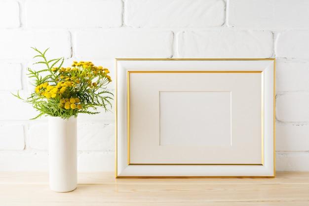 Maqueta de marco dorado decorado cerca de paredes de ladrillo pintadas