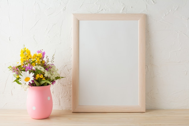 Maqueta de marco con flores silvestres en florero rosa