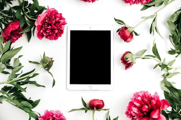 Maqueta de marco de flores de tableta y peonías en superficie blanca