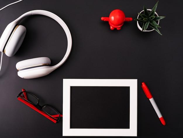 Maqueta, marco de fotos, auriculares, gafas, pluma y cactus