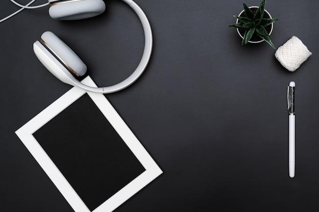 Maqueta, marco de fotos, auriculares, lápiz y cactus. escribe un objeto sobre fondo negro.