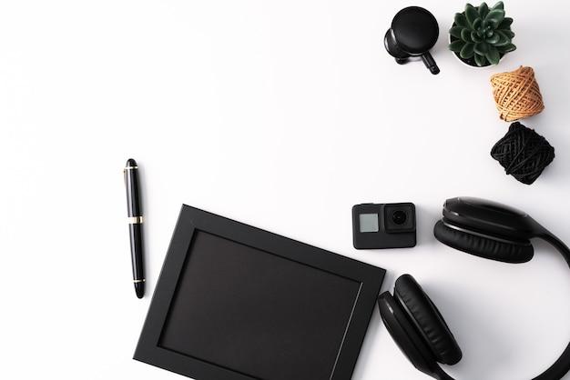 Maqueta, marco de fotos, cámara de acción, auriculares, bolígrafo y cactus.