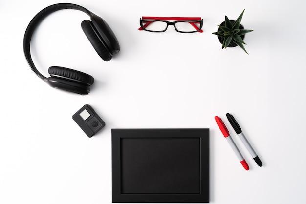 Maqueta, marco de fotos, cámara de acción, auriculares, gafas, lápiz y cactus, objeto rojo y negro sobre fondo blanco