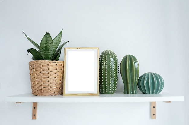Maqueta de marco de fotos dorado en un estante con flores de interior y figuras de cactus.
