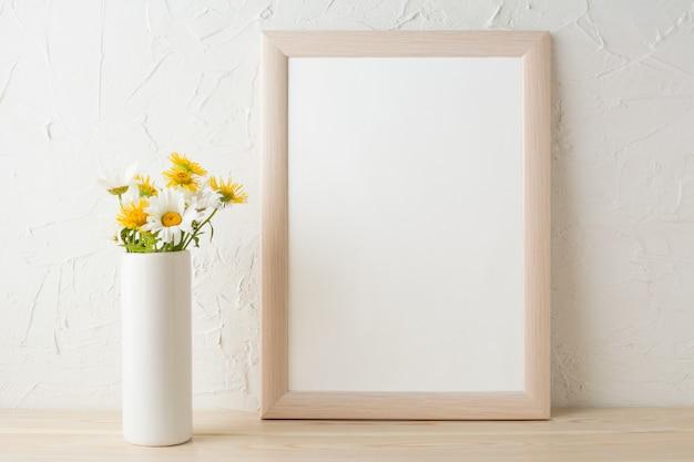Maqueta de marco con manzanillas blancas y amarillas en florero