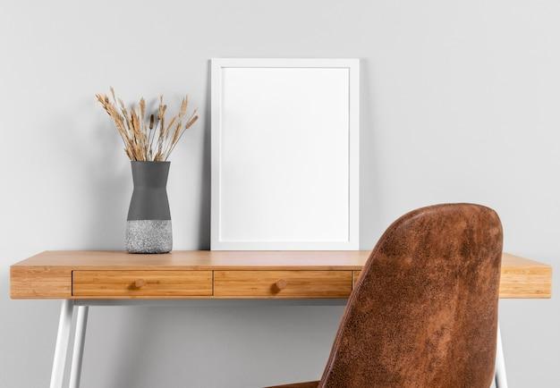 Maqueta de marco en la mesa junto al jarrón