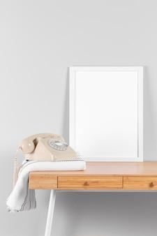 Maqueta de marco en mesa con teléfono