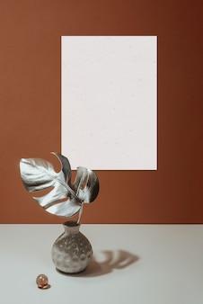 Maqueta de marco y monstera de hojas en un jarrón sobre un fondo de pared de terracota. bodegón duro con parasoles.