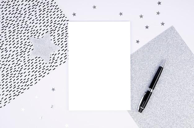 Maqueta de marco plateado de vista superior tarjeta de papel en blanco y bolígrafo negro con arreglo de adornos navideños.