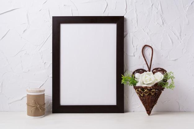 Maqueta de marco de póster marrón negro con rosas en maceta de mimbre