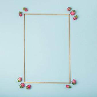 Maqueta marco vacío con capullos de rosa sobre fondo azul.