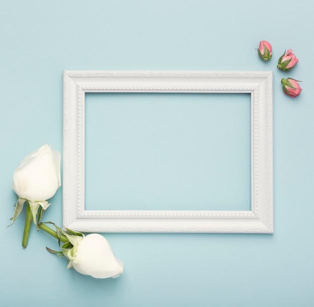 Maqueta marco vacío horizontal blanco con capullos de rosa sobre fondo azul.
