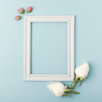 Maqueta marco vacío vertical blanco con capullos de rosa sobre fondo azul.